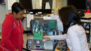 Two student interns working on computer board