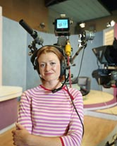 A female TV camera operator on a studio set.
